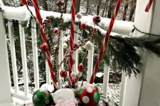 a bold outdoor Christmas decoration of a vase iwth fir branches, bright ornaments and large candy canes is whimsical and bright