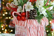 a bright Christmas centerpiece of a vase with candy canes, greenery, white blooms, snowy pinecones, candy canes and branches