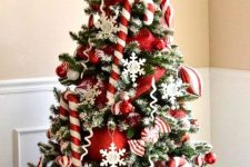 a bright and chic Christmas tree with candy canes, red ornaments, snowflakes, twigs and berries is amazing