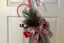 a bright door decoration of fir branches, bright bows and candy canes can be made in some minutes and looks fun and cool