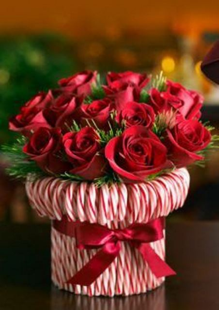 a bright holiday centerpiece -a vase wrapped with candy canes and with greenery and red roses is a very refined and chic idea
