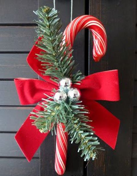 a candy cane with a red bow, fir twigs and bells is a lovely Christmas decoration or ornament