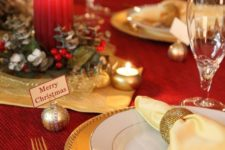 a chic red and gold Christmas table with a greenery and candle centerpiece, gold chargers and cutlery, mini candles and ornaments