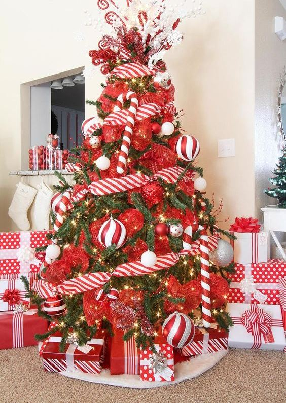 a colorful Christmas tree decorated with lights, red and red and white ribbons, overiszed candy canes and ornaments is ultimate fun