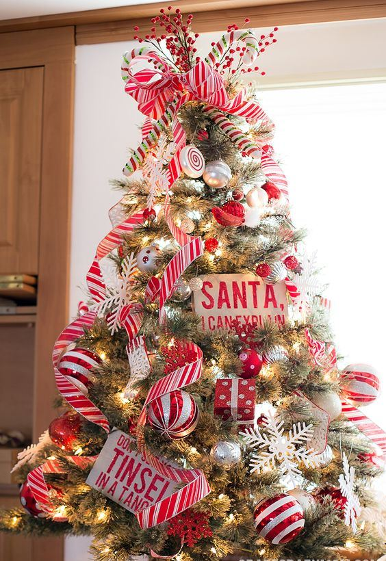 a colorful Christmas tree decorated with striped and silver ornaments, ribbons, candy ornaments and berries is fun