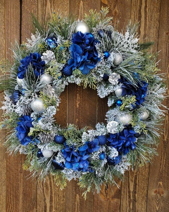 a frozen Christmas wreath with bold blue flowers, bows and silver and blue ornaments is a pretty and chic idea