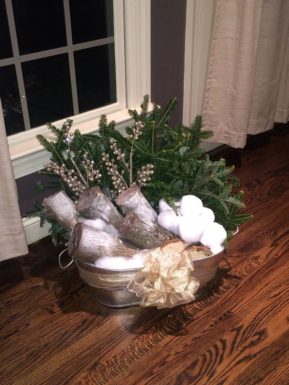 a galvanized bathtub with firewood, snowballs, fir branches, berries and a bow is a cool outdoor decoration for Christmas
