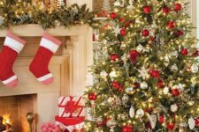 a large Christmas tree with red, gold and mother of pearl ornaments, lights and lots of red and white gift boxes