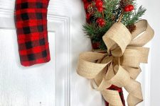 a large bright plaid candy cane wreath with a burlap bow, fir branches, berries and pinecones is a lovely idea for outdoors