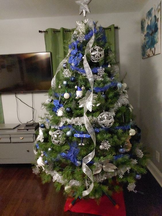 a lovely Christmas tree with blue and silver decor   ribbons, ornaments, snowflakes and stars is an amazing idea