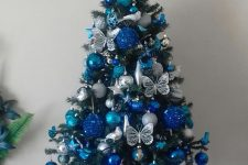 a lovely tabletop Christmas tree with silver, bold blue and navy ornaments and butterflies is an amazingly chic and bold idea