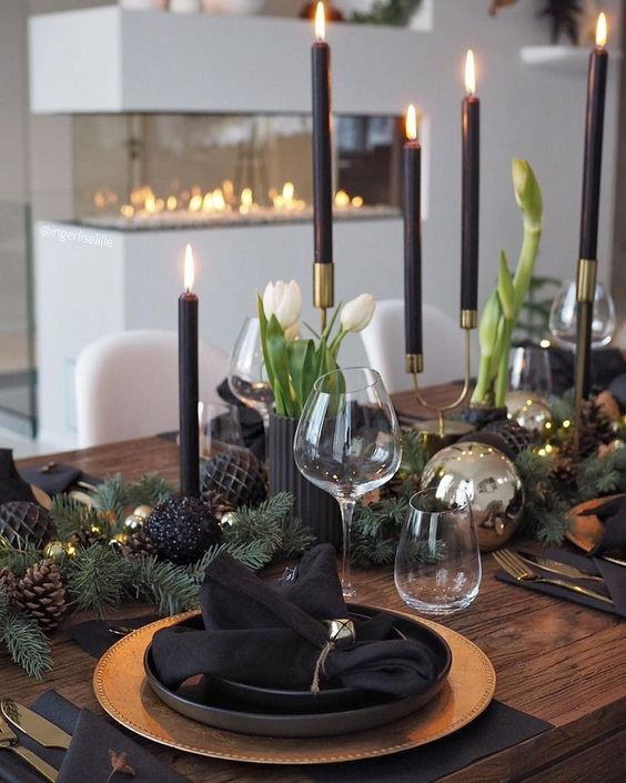 a modern holiday table with gold charger, cutlery, black and shiny ornaments, black candles and white blooms plus bells