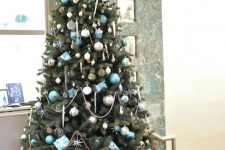 a pretty Christmas tree with silver and tiffany blue ornaments, stars, lights, beads and gifts is a very chic and glam idea