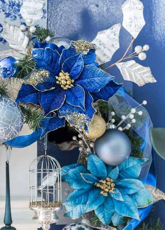 a refined Christmas wreath with silver, gold ornaments and bold blue and light blue blooms and a silver cage with a bird