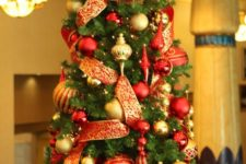 a refined red and gold Christmas tree with a large bow on top, lots of ornaments and lights