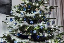 a shining Christmas tree with lights, blue, navy and silver ornaments and stars is a beautiful and chic idea