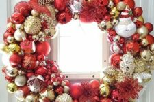 a shiny Christmas wreath fully made of ornaments, in gold, silver and red, of various sizes and looks