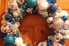 a shiny Christmas wreath of tiffany blue, navy, white and silver ornaments and ribbons is a pretty decoration to rock