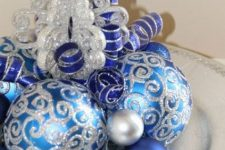a simple Christmas centerpiece of a silver plate, silver, silver glitter and blue ornaments is a stylish and bright decoration