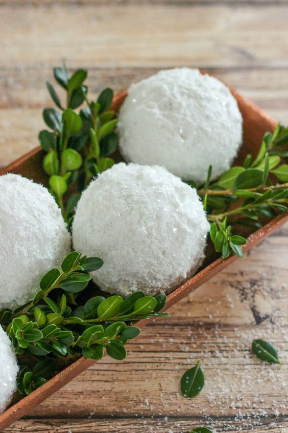 a simple centerpiece of a wooden tray with greenery and shiny snowballs can be easily made last minute and looks cool