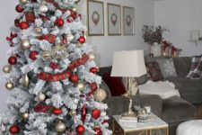 a snowy Christmas tree with gold and red ornaments, plaid ribbons and a silver tree topper