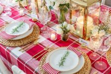 a stylish Christmas table with a red plaid tablecloth, gold lanterns, red and white blooms and woven placemats