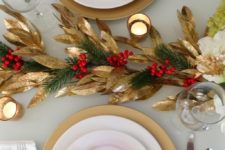 a stylish red and gold Christmas table with gold foliage, evergreens and berries, red blooms and candles