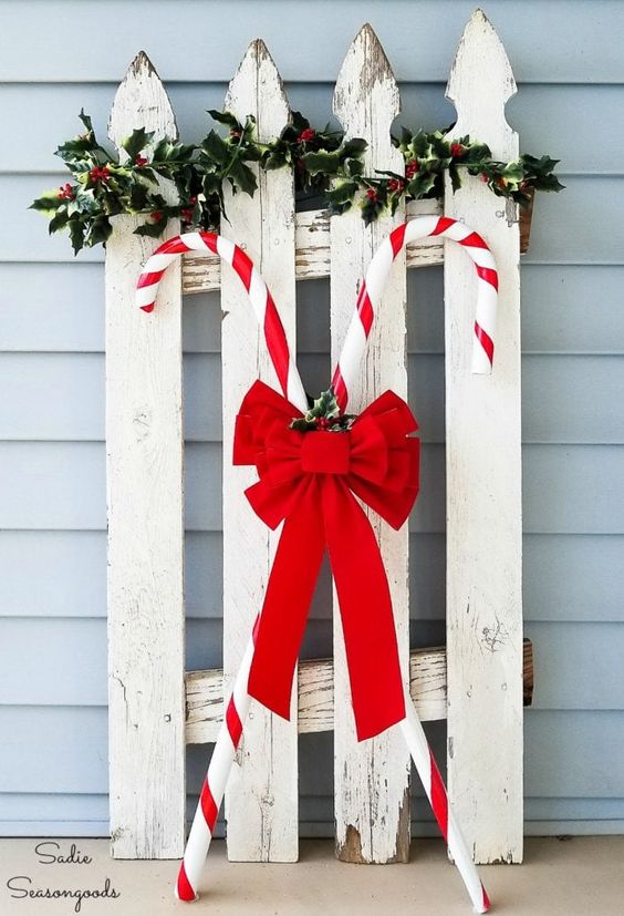 a vintage sleigh with greenery and candy canes accented with a large red bow is a pretty and cool rustic decoration for outdoors
