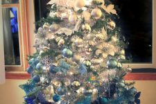 an ombre Christmas tree from white to light blue and navy and with a large white and silver bow on top is amazing
