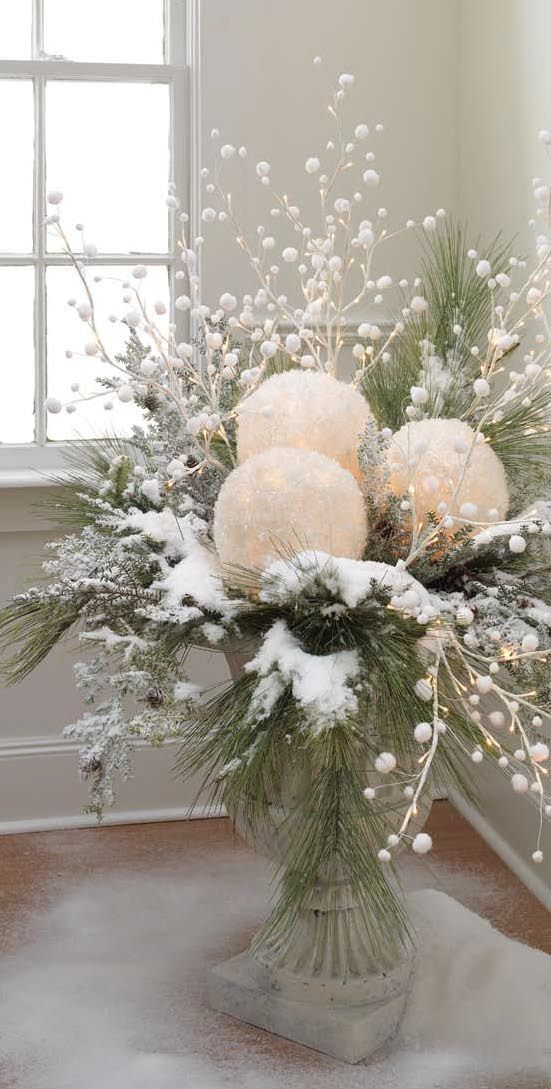 an outdoor Christmas arrangement of oversized snowballs, fir branches, snowy branches and berries plus lights