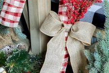 an oversized plaid candy cane wreath with a burlap bow and some berry branches is a lovely and bold decoration for outdoors and not only