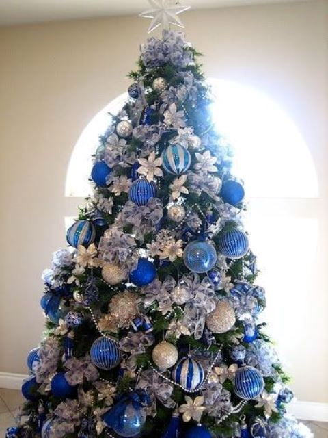 bold Christmas tree decor with silver, blue and navy ornaments, fabric blooms and a star topper is a cool idea for holidays