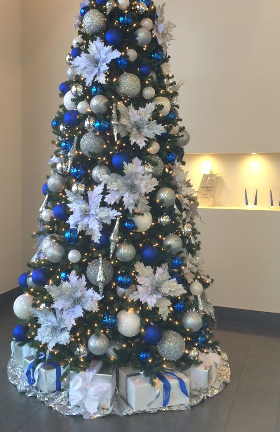 bright Christmas tree decor with lights, white fabric blooms, silver and blue ornaments plus gifts under the tree is a lovely idea