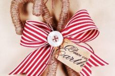 classy rustic Christmas ornaments – candy canes wrapped with twine, with buttons and a striped bow are amazing