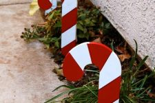 cool outdoor holiday decor – growing greenery accented with candy canes looks very bright and very cool