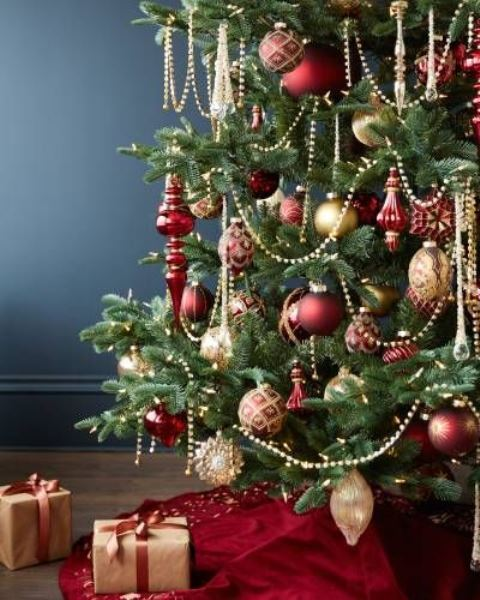 elegant red and gold Christmas tree decor with beads, ornaments, lights and gift boxes