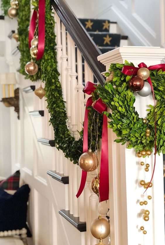 gold, red and brown ornaments, evergreens and deep red bows for decorating the railing