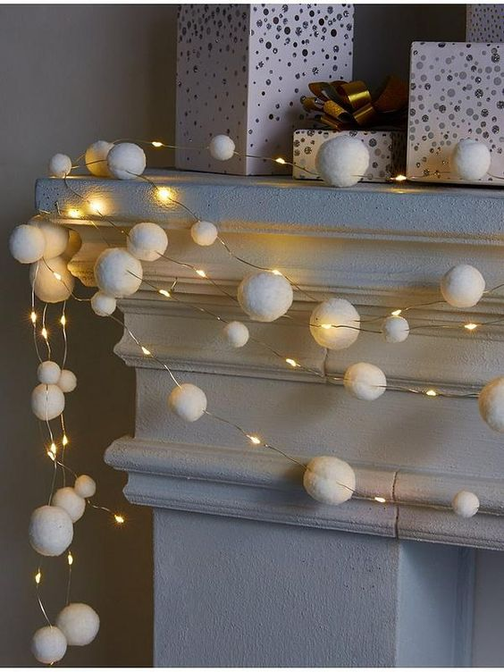 lights and snowball garlands on the mantel will add a holiday feel to your space at Christmas and you can craft them yourself