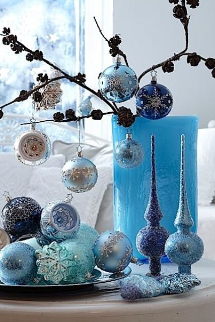 lovely blue and silver Christmas decor with a branch with ornaments, ornaments on the plate and some tree toppers