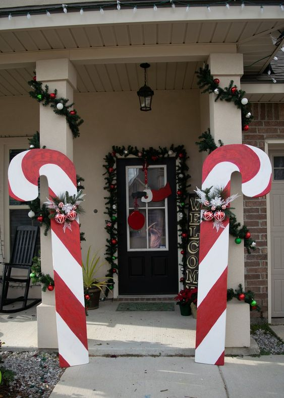 oversized candy canes with ornaments and fir branches will make your home entrance and make it look bold and cool