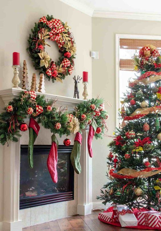 red, gold and green Christmas decor with stockings, a wreath and a tree with ribbons and ornaments