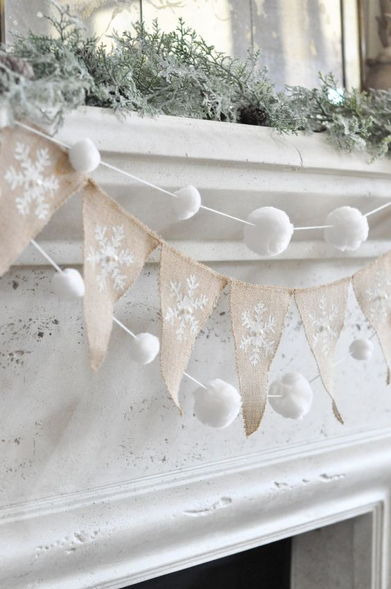 snowy Christmas mantel decor with a burlap runner, snowball garlands and snowy greenery is very chic and elegant