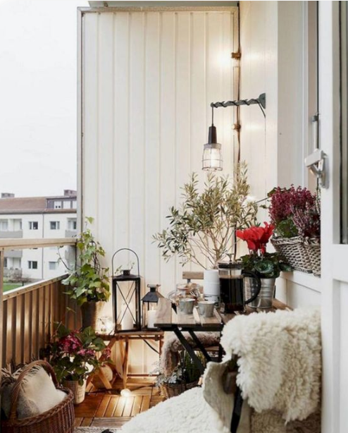 a Christmas balcony with lush bright blooms, greenery in pots, candle lanterns and faux fur here and there