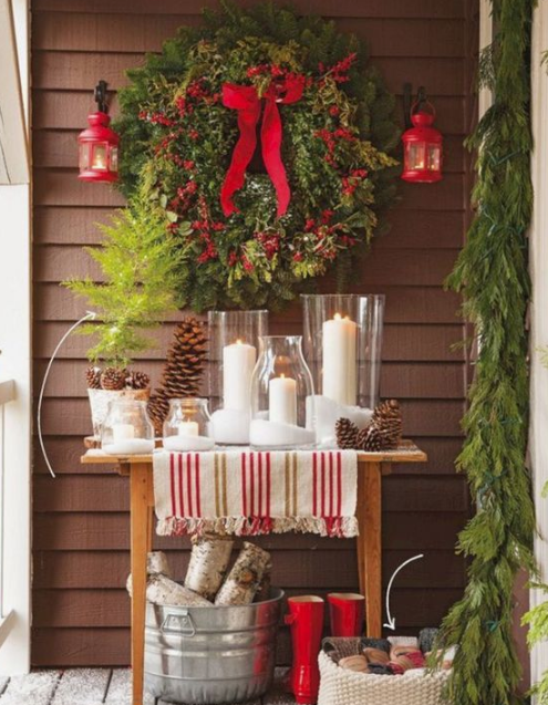 a console table with pillar candles, pinecones, an evergreen wreath with red berries and bows, red lanterns and firewood in a bucket