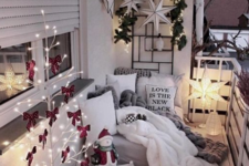 a cozy little balcony with a light tree with red bows, some candle lanterns, a star lamp, stars and greenery on the wall and fur and knit textiles