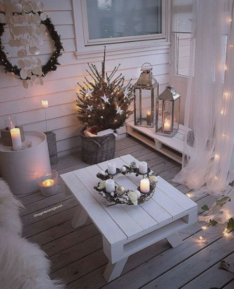 a cozy little winter balcony with shiplap furniture, faux fur, candles in candleholders and candle lanterns, a mini tree with stars and a wreath