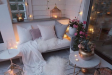 a cozy winter balcony with faux fur, candles in lanterns and candleholders, lights and potted blooms