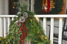 lush evergreen garlands with berries, pinecones, lights and a matching evergreen wreath with a large red bow