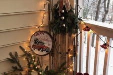 red rubber boots, some firewood and evergreens in a bucket and a vintage sleigh with bells and evergreens plus lights around