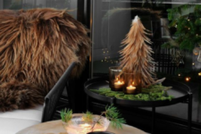 side tables wth evergreens, a mini Christmas tree, candles in dark candleholders and faux fur throws on the chairs